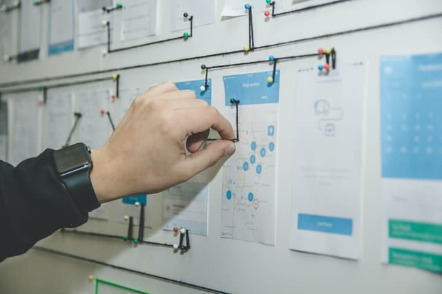 A web designer mapping out user interactions on a whiteboard.