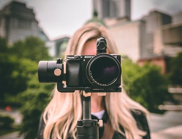 A woman holding a camera and thinking about the ways to make your website SEO friendly in 2021.